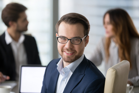 Head shot portrait of confident businessman or business owner at workplace, smiling man sitting at briefing and looking at camera. Colleagues discuss in background.