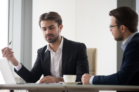 Two caucasian men in suits are discussing and planning project. Coworkers or manager and subordinate are sitting at the table and looking at monitor. One men explain arguments in favor of his opinion
