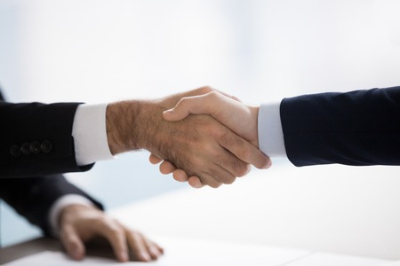 Two men shaking hands. Partners or team members consolidating common collaboration with formal handshake. Good deal, successful project confirmation. Close up, HR , help, first impression concept