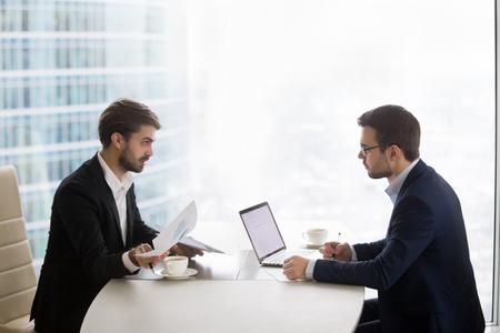 Dos hombres caucásicos sentados uno frente al otro en la mesa y discutiendo los resultados del proyecto. Los socios o el gerente y el subordinado realizan una cita de evaluación del desempeño en la oficina o sala de reuniones Foto de archivo