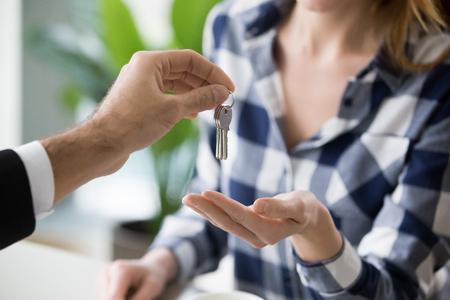 Junge Frau, die Schlüssel zur neuen Wohnung vom Makler erhält. Familie kauft, mietet neues Haus. Kunden oder Mieter kaufen oder mieten Immobilien, Nahaufnahme