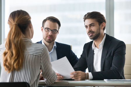 Two male hr managers at interview with female applicant. Man with resume in hands asks questions to candidate. Hiring, staff recruiting process. Stock Photo