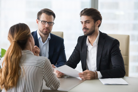 Two hr managers looking with disbelief at female applicant. Skeptic employer. Candidate lied in resume, bad cv. No hiring, staff recruiting process, bad first impression.