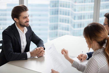 Young man at job interview answering questions of employer. Two HR managers talking with successful candidate for vacancy. Hiring, staff recruiting process. Stock Photo - 111159479