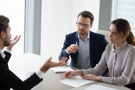 Two hr managers listen attentively to candidate for vacancy. Job seeker at job interview answering questions of employer. Hiring, staff recruiting process. Stock Photo