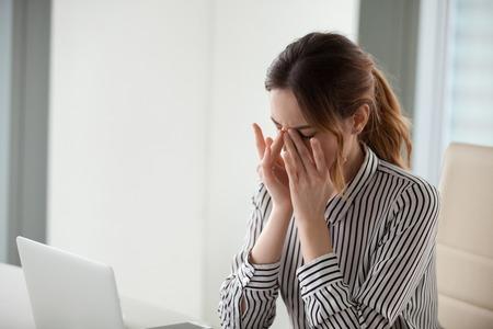 Vermoeide jonge vrouw die neusbrug masseert op het werk. Zakenvrouw ervaart ongemak van lang werken op de computer. Slecht oog visie concept Stockfoto