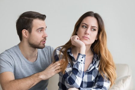 Wife offended by husband, man asks for forgiveness. Angry depressed young woman has no desire to talk, listening to lies of her boyfriend saying sorry. Troubles in family, misunderstanding, distrust Stock Photo
