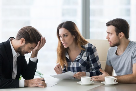 Annoying customers at meeting with realtor, financial advisor, banker ask questions or argue. Tired embarrassed employee at meeting with young couple buying, renting house, taking loan, mortgage