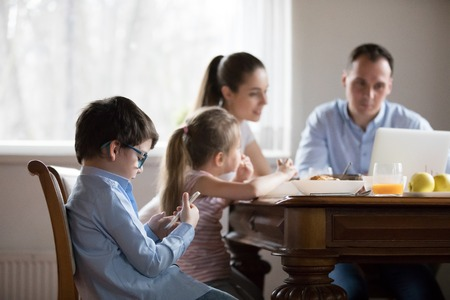 Family with little children sitting in kitchen during breakfast. Wife husband looks at laptop, focus on small son in glasses use cellular. Mobile phone overuse and addiction gadgets dependency concept Stock Photo