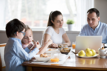 Family with little children sitting in kitchen during breakfast. Wife husband looks at laptop, focus on small son and daughter using cellular. Devices overuse and addiction gadgets dependency concept Stock Photo