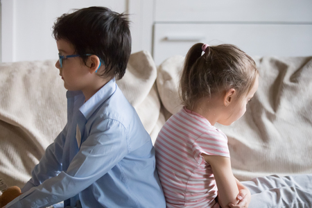 Offended little preschool siblings after quarrel, punishment sitting together on sofa in living room at home dont look at each other. Sulky sister and brother have conflict feeling frustrated unhappy 免版税图像