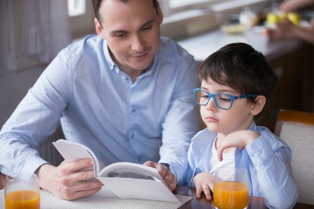 Man and boy sitting together at table in the kitchen at home. Father holding book reading fairytale little adorable son with eyeglasses listen with interest. Concept of education, development of child