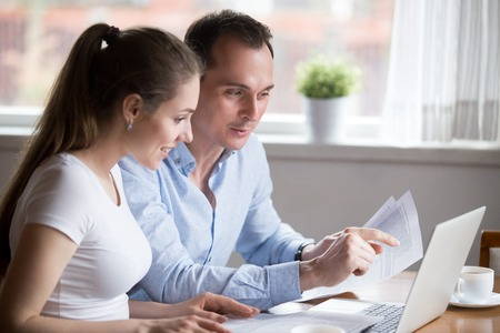 Happy positive millennial spouses sitting at the desk at home read notice paper check bills or bank account balance feeling happy and glad. Couple have income or last loan payment good news concept