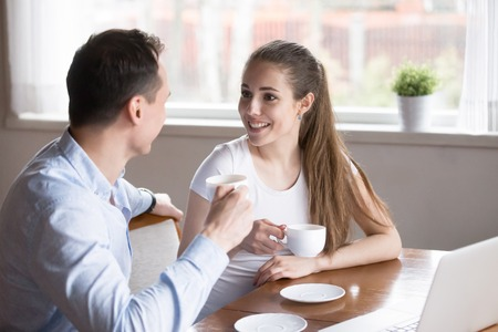 Beautiful positive millennial couple in love sitting in kitchen drinking morning coffee at home. Young childfree wife and husband talking about upcoming work day or discussing about plans on weekend Stock Photo