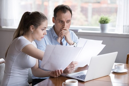 Stressed millennial married couple sitting at the desk at home use laptop checking documents unpaid bills, taxes, due debt, bank account balance. Bankruptcy lack of money financial problems concept