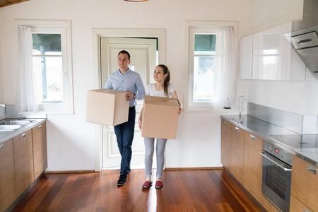 Tausendjährige Ehefrau und Ehemann in voller Länge halten Kartons mit Gegenständen, die in der modernen Küche zu Hause stehen. Attraktives glückliches Paar kaufte neues Haus. Umzug Relocate Day Hypotheken- und Mieterkonzept