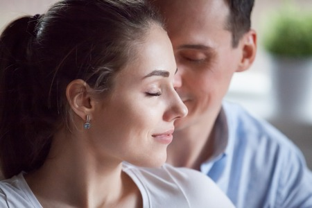 Close up portrait attractive candid happy young spouses couple female and male with closed eyes enjoy spend time together close to each other. Sincere feelings love and romantic relationships concept