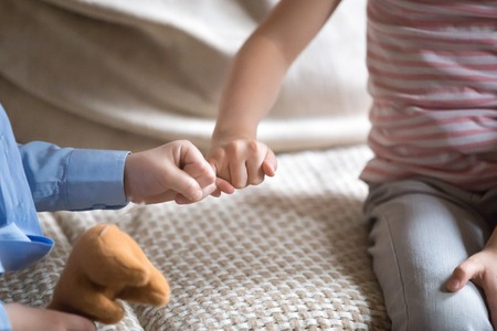 Small kids sitting on couch at home little children reconciling after fight or quarrelling making peace with fingers gesture joining pinkies symbol of no more arguing swear be friends forever concept.
