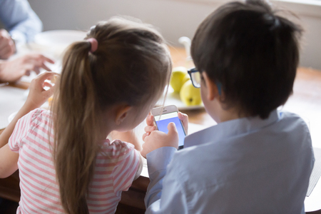 Little brother and sister use smartphone sitting in kitchen at dining room, kids rear view over shoulder close up. Daughter son have fun looking at mobile phone screen play games watch video cartoons Stock Photo