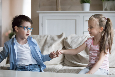 Adorable preschool kids sitting on sofa at home. Little children reconcile after fight or quarrelling making peace with hand gesture hold hands joining pinkies swear no more arguing be friends forever Archivio Fotografico