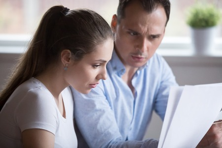 Stressed spouses read letter document notification about unpaid bills taxes or unexpected expenses or due debt. Couple feels frustrated and confused. Bankruptcy lack of money financial problem concept