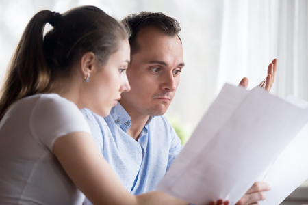 Stressed spouses read letter receive notice about unpaid bills taxes, forfeits. Close up of frustrated wife and husband have financial problems unexpected expenses. Bankruptcy lack of money concept