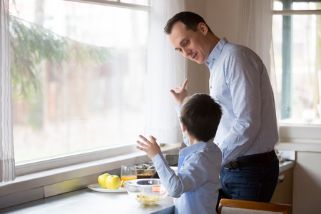 Man and little boy preparing dinner standing in the kitchen at modern home. Loving single father teach preschool little son cooking healthy vegetarian food. Upbringing and development of child concept
