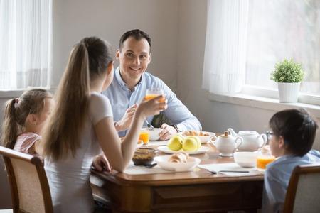Jeune famille heureuse avec de petits enfants d'âge préscolaire adorables assis à la salle à manger ensemble dans la cuisine le matin à la maison communiquant parler prendre le petit déjeuner manger des aliments sains boire du jus d'orange.