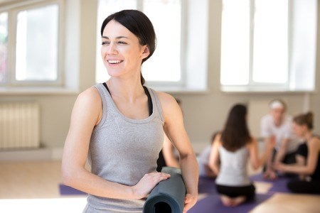 Millennial brunette instructor attractive female holding yoga mat smiling standing looking away, group of sportive girls and guys on background. People take a break during workout or seminar workshop
