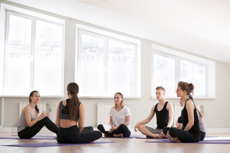Group at yoga sport seminar in professional training studio. Girls and guys sitting together listen teacher coach ask questions communicating learn more about spiritual mental physical yoga practices Reklamní fotografie