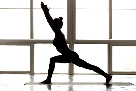 Young sporty woman practicing yoga, doing Warrior one exercise, Virabhadrasana I pose, working out concept, wearing sportswear black pants, top, indoor full length, at yoga studio, side view silhouette Stok Fotoğraf