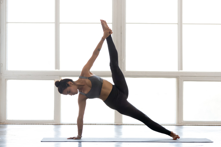 Young yogi attractive woman practicing yoga, doing Full Version of Vasisthasana exercise, Side Plank pose, working out, wearing sportswear, grey pants, top, indoor full length, at yoga studio Stock Photo