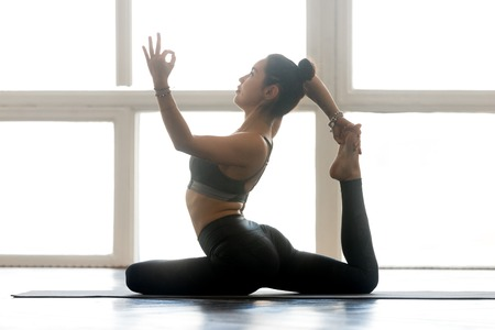 Young sporty attractive woman practicing yoga, doing One Legged King Pigeon exercise, Eka Pada Rajakapotasana pose, working out, wearing sportswear, grey pants, top, indoor full length, at yoga studio Stock Photo