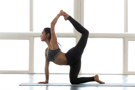 Young sporty attractive woman practicing yoga, doing tiger exercise, Bird dog pose, working out, wearing sportswear, grey pants, top, indoor full length, at yoga studio, side view
