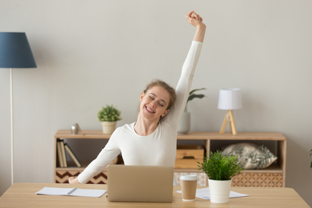 Happy satisfied young woman sitting at the desk in office room or home at workplace finish work, stretching out with raised hands. Millennial female relaxing after working hard day, no stress concept 版權商用圖片 - 111159927