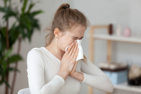 Jonge duizendjarige zieke vrouw die alleen zit op het werkkantoor niest met een zakdoek in haar hand en blaast haar loopneus af. Student meisje heeft seizoensgebonden allergie of chronische sinusitis ziekte concept