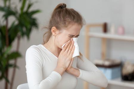 Joven mujer enferma milenaria sentada sola en la oficina de trabajo estornuda sosteniendo un pañuelo de papel y soplando limpiando su nariz que moquea. Chica estudiante tiene alergia estacional o concepto de enfermedad de sinusitis crónica