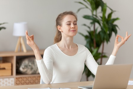 Young millennial woman sitting in office opposite computer taking break for meditation yoga practice. Thinking, focusing, stress relief, healthy good habits, mental health, mindful lifestyle concepts