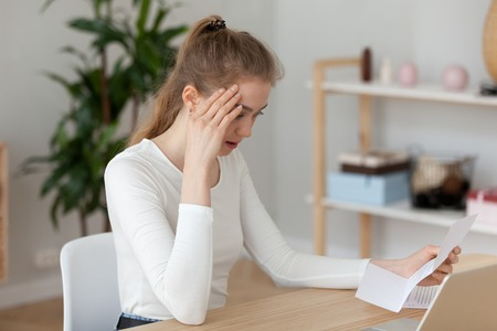 Frustrated millennial woman sitting at the desk in office or at home read notification about debt or not recruited. Stressed student holding letter about scholarship refusal expulsion from high school Stock Photo