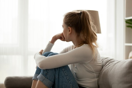 Side view young woman looking away at window sitting on couch at home. Frustrated confused female feels unhappy problem in personal life quarrel break up with boyfriend or unexpected pregnancy concept