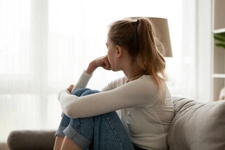Widok z boku młoda kobieta, patrząc od okna, siedząc na kanapie w domu. Sfrustrowana zdezorientowana kobieta odczuwa nieszczęśliwy problem w życiu osobistym, kłótnia, zerwanie z chłopakiem lub nieoczekiwana koncepcja ciąży Zdjęcie Seryjne