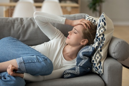 Close up young attractive woman lying at home on couch alone. Frustrated after call, female feels unwell, suffering from headache. Girl has problems with boyfriend or unexpected pregnancy concept
