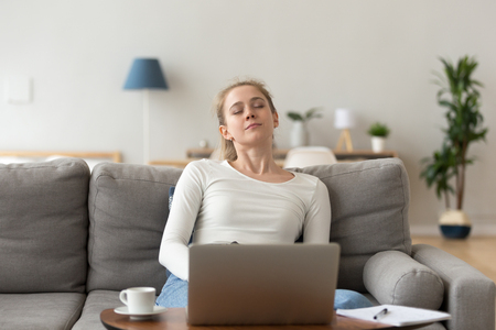 Attractive young tired millennial student woman sitting on couch in living room at home opposite of computer sleeping. Overworked fatigued serene female nap after studying. Hard working day concept Stock Photo