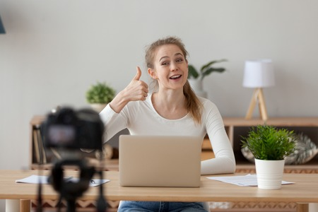 Happy woman sitting at the desk office or home recording video smiling showing thumbs up sign looking at camera. Blogger girl sharing good positive mood for viewers. Freelancer working online concept Reklamní fotografie