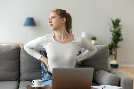 Tired student girl suffers from backache feeling badly, sitting on couch in living room at home. Has a back pain after studying at the computer for a long time. Sedentary work and bad posture concept