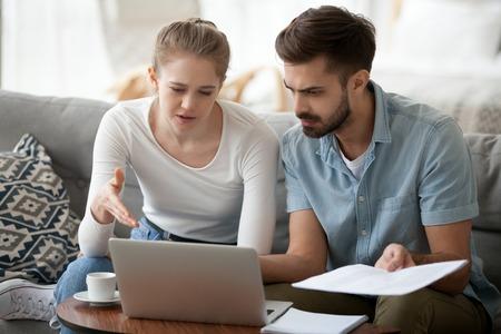Frustriertes Ehepaar hat finanzielle Probleme Frau und Mann erhielten schlechte Nachrichten von der Bank über Schulden hohe Steuern. Tausendjährige Frau und Mann, die Post auf dem Laptop lesen, der Papierbrief-Haushaltsrechnung hält