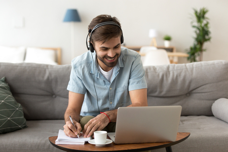 Man sitting on couch in living room at home enjoying studying using laptop and headset looking at device screen listening audio making some notes. Male has lesson online e-learning in internet concept