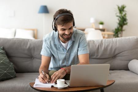 Mann sitzt auf der Couch im Wohnzimmer zu Hause und genießt das Lernen mit Laptop und Headset und schaut auf den Bildschirm des Geräts und hört Audio, um einige Notizen zu machen. Mann hat Online-E-Learning-Unterricht im Internet-Konzept
