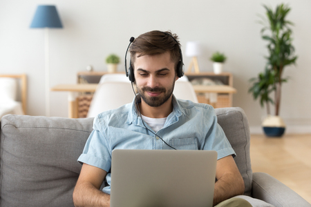 Millennial man sitting on couch in living room at home. Satisfied male studying chatting online using computer and headset watching educational video, learning foreign languages on internet concept