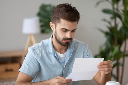 Frustrated millennial man sitting at the desk in office holding reading notification about debt or not recruited. Stressed student holding letter about scholarship refusal expulsion from high school